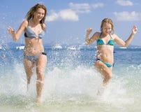 2 mujeres que corren en la playa Imágenes de archivo libres de regalías