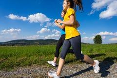 Mujeres que corren, salto al aire libre Foto de archivo libre de regalías
