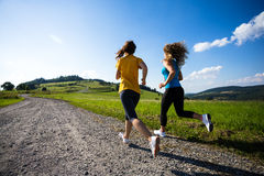 Mujeres que corren, salto al aire libre Imagenes de archivo