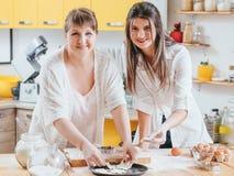 Mujeres que cuecen la cacerola de la estrella de la pasta de pasteles de las galletas fotos de archivo