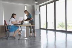 Mujeres que discuten el documento en el escritorio en oficina vacía Imagen de archivo