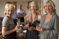 Mujeres que disfrutan de Champán en un partido de cena Imágenes de archivo libres de regalías