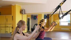Mujeres que ejercitan usando lazos de las correas de la aptitud metrajes