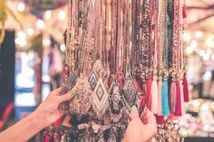Mujeres que eligen el bijouterie en la tienda Isla de Bali Manos de la mujer fotos de archivo libres de regalías