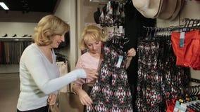 Mujeres que eligen el vestido durante compras en la tienda metrajes