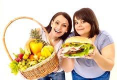 Mujeres que eligen entre la fruta y la hamburguesa. Fotos de archivo