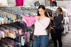 Mujeres que eligen la ropa interior en tienda Imagen de archivo