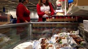 Mujeres que eligen las comidas dentro de la tienda de Ikea metrajes
