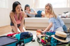 Mujeres que embalan las maletas para las vacaciones juntas en casa, consiguiendo listas para viajar concepto Imágenes de archivo libres de regalías