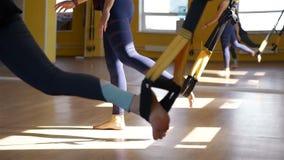 Mujeres que entrenan con las bandas de la resistencia en un gimnasio almacen de video