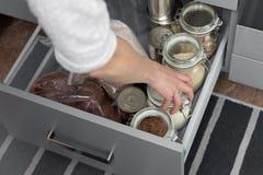 Mujeres que escogen un artículo del aparador del almacenamiento Concepto elegante de la organización de la cocina fotografía de archivo