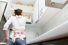 Mujeres que escogen un artículo del aparador del almacenamiento Concepto elegante de la organización de la cocina fotos de archivo libres de regalías