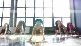 Mujeres que estiran y que se relajan en clase de la yoga almacen de metraje de vídeo