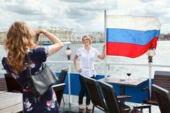 Mujeres que fotografían con el indicador ruso en cubierta de la nave Fotografía de archivo libre de regalías