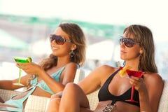 Mujeres que gozan en barra con vidrios de martini Fotos de archivo libres de regalías