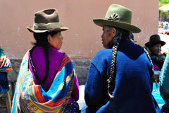 Mujeres que hablan en el mercado en Pisac, Perú de domingo. Foto de archivo