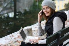 Mujeres que hablan en el teléfono y que pulsan en la computadora portátil Fotografía de archivo libre de regalías