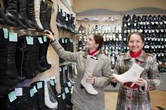 Mujeres que hacen compras en el almacén de zapato de la manera Fotos de archivo libres de regalías
