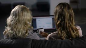 Mujeres que hacen compras en línea con el ordenador portátil y la tarjeta de crédito metrajes
