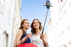 Mujeres que hacen compras y que toman el selfie por smartphone Imágenes de archivo libres de regalías