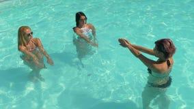 Mujeres que hacen el gimnasio de la aguamarina en la piscina en un centro turístico de vacaciones metrajes
