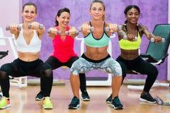 Mujeres que hacen las posiciones en cuclillas que llevan a cabo pesas de gimnasia en el grou funcional del entrenamiento imagen de archivo libre de regalías