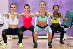 Mujeres que hacen las posiciones en cuclillas que llevan a cabo pesas de gimnasia en el grou funcional del entrenamiento imagen de archivo