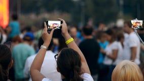 Mujeres que hacen los vídeos en sus smartphones en la muchedumbre en festival de música al aire libre del verano metrajes
