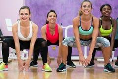 Mujeres que hacen posiciones en cuclillas durante clase del grupo del entrenamiento en la salud moderna c imagen de archivo libre de regalías