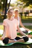 Mujeres que hacen yoga al aire libre en la salida del sol Meditación de la mañana fotos de archivo