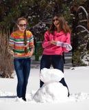 Mujeres que juegan con el muñeco de nieve Imagen de archivo