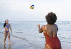 Mujeres que juegan a voleibol en la playa Foto de archivo libre de regalías