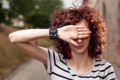 Mujeres que la ocultan ojos por la palma abierta Foto de archivo