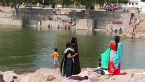 Mujeres que lavan las ropas coloridas en el río en Orchha, Madhya Pradesh, la India metrajes