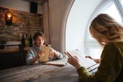 Mujeres que leen el menú en restaurante Imágenes de archivo libres de regalías