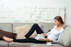 Mujeres que leen un libro en el sofá Fotografía de archivo