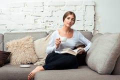 Mujeres que leen un libro en el sofá Fotos de archivo libres de regalías