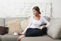 Mujeres que leen un libro en el sofá Imágenes de archivo libres de regalías