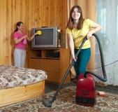 Mujeres que limpian en sala de estar Fotografía de archivo libre de regalías