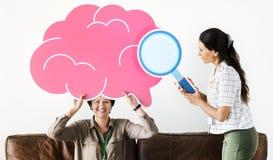 Mujeres que llevan a cabo iconos rosados de la nube Fotos de archivo