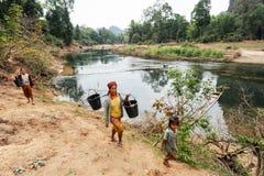 Mujeres que llevan los cubos de agua del río Fotografía de archivo