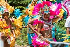 Mujeres que llevan los trajes y el paseo emplumado de los tocados en desfile del Caribe imagenes de archivo