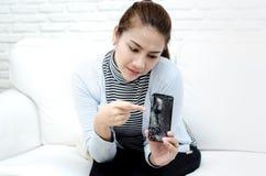 Mujeres que llevan una camisa azul que sostiene un teléfono móvil quebrado foto de archivo
