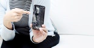 Mujeres que llevan una camisa azul que sostiene un teléfono móvil quebrado imagenes de archivo