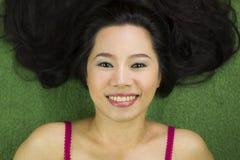 Mujeres que mienten en la hierba verde, una sonrisa divertida hermosa y temporaria, mujer tailandesa que coloca en hierba verde fotografía de archivo libre de regalías