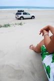 Mujeres que miran el coche conducir en la playa Fotos de archivo