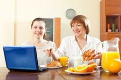 Mujeres que miran el email en ordenador portátil durante el desayuno Fotos de archivo libres de regalías