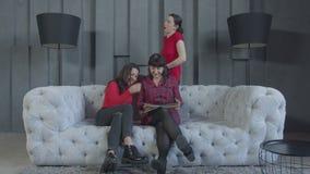 Mujeres que miran las fotos el sentarse en el sofá en casa almacen de video