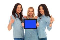 3 mujeres que muestran la pantalla de la tableta y hacen muy bien Foto de archivo