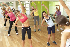 Mujeres que participan en clase de la aptitud del gimnasio Foto de archivo